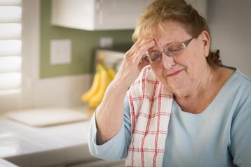 Sad Crying Senior Adult Woman At Kitchen Sink