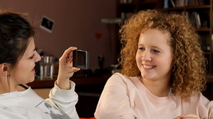 Young friends taking a picture by phone - tracking shot
