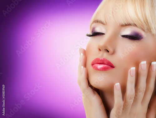 Beautiful woman with manicure and purple makeup