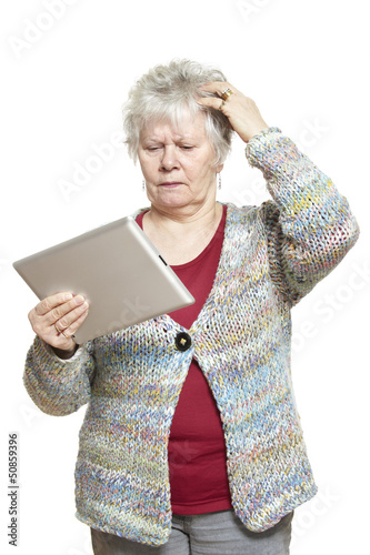 Senior woman using tablet computer looking confused