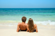 Young couple sitting together on a sand by sea and looking to a