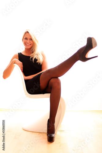 Model sitzt auf weißem Stuhl