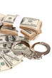 Handcuffs and packs of dollars on white background close-up