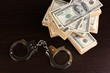 Handcuffs and packs of dollars on wooden table close-up