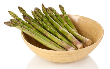 Fresh asparagus in wooden bowl isolated on white.