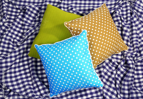 Three various pillows on plaid