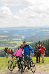 Posing cyclist couple on mountain with bikes
