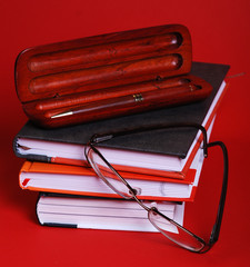 books,pens and glasses on red background