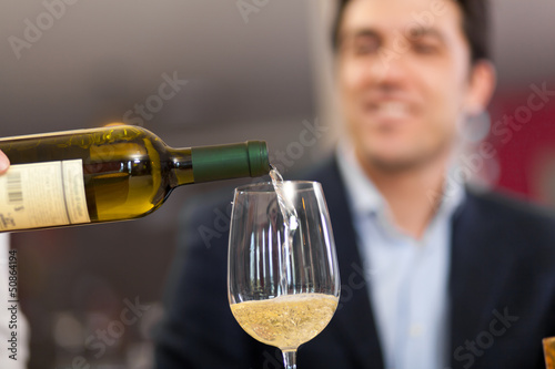 Waiter pouring wine to a man
