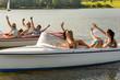 Waving friends sitting in motorboats summertime