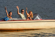 Young people waving from motorboat