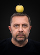 man with a green apple on his head