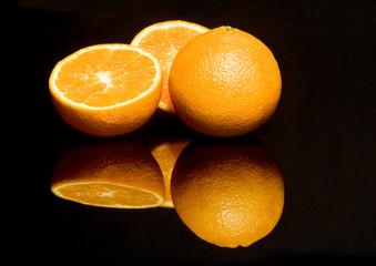 Drei Orangen spiegeln sich auf schwarzer Flaeche