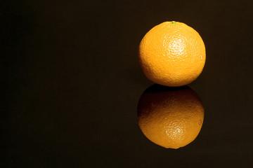 Eine Orange spiegelt sich auf schwarzer Flaeche..