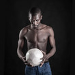 Young African man with a white soccer ball on black background.