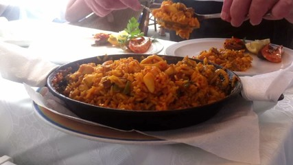 Waiter serving seafood paella in the pan, typical Spanish dish (