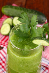 Glass of cucumber juice on wooden table
