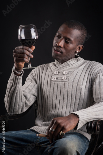 Confident portrait of african man tasting glass of red wine.
