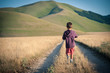 Kid walking alone outdoors. Castelluccio di Norcia, Italy.