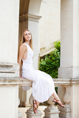 Young attractive blond girl in the long white dress