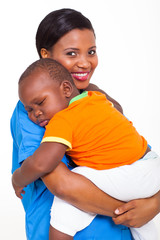 portrait of young african nurse carrying sleeping baby boy
