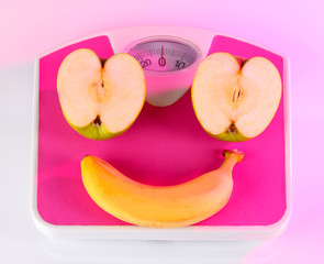 Apple and banana on scales on light background