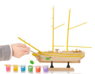 Boy paints model sailing ship on white