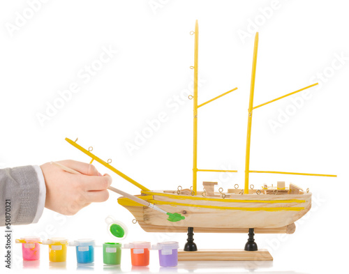 Boy paints model sailing ship on white