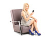 Woman with a mobile phone, sitting in an armchair
