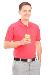 Smiling young man posing with a glass of orange juice