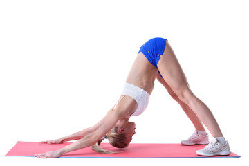 Flexible woman doing stretching exercises on mat