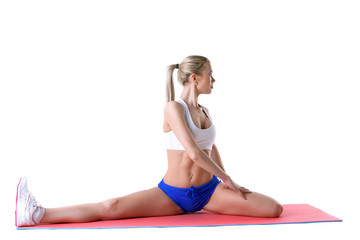 Slim blonde doing stretching exercises in studio