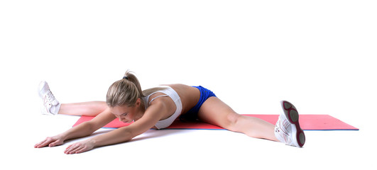 Athletic girl doing stretching exercises on mat