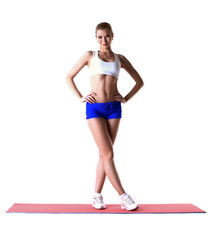Beautiful slim woman posing on gymnastic mat
