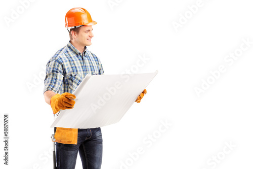 Male engineer with helmet and tool belt holding a blueprint