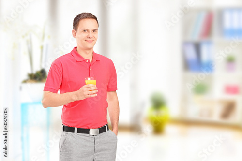 Smiling man posing with a glass of orange juice at home