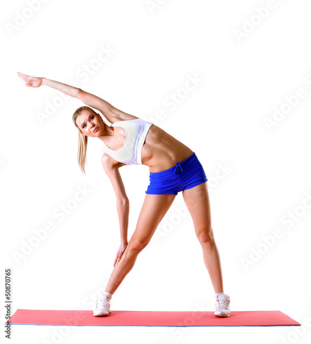 Beautiful woman practices aerobics in studio