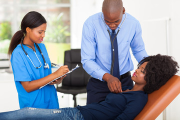 african american doctor examining female patient