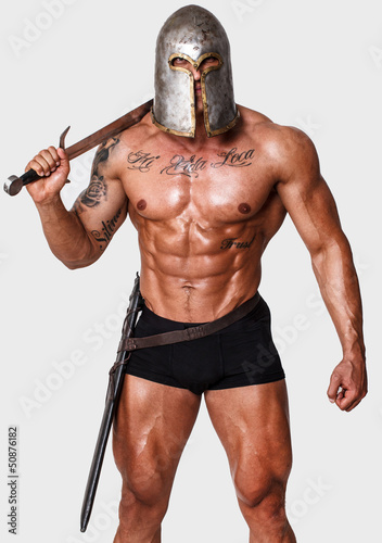 Hot warrior in black pants is holding sword in his shoulder