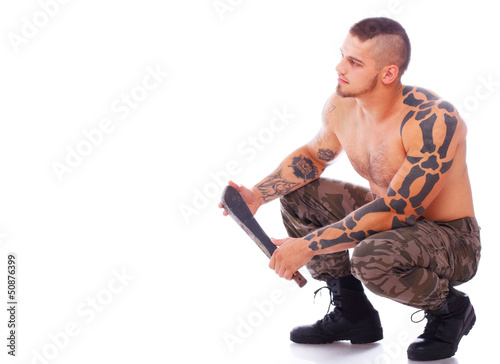 Russian man with machete is sitting and leaning on his feets