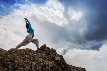 Woman doing yoga warrior pose on mountain