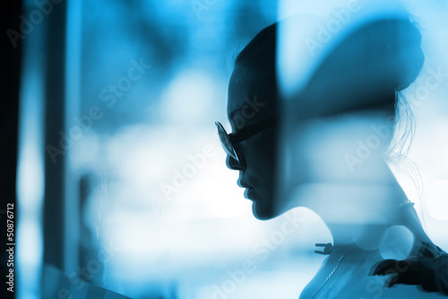 Fashion woman profile silhouette behind glass