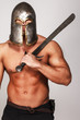 Shirtless warrior in helmet and with sword