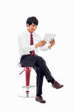 Young Asian business man using a pad PC sitting on the chair.