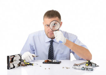 Hardware repairman with a magnifying glass on white