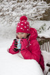 Young girl enjoying a warm drink in garden