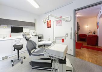 Moderner Zahnarztstuhl mit Wartezimmer im Hintergrund