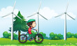 A boy riding with his bike near the windmills