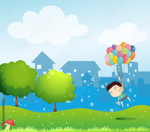 A boy floating in the air with the balloons