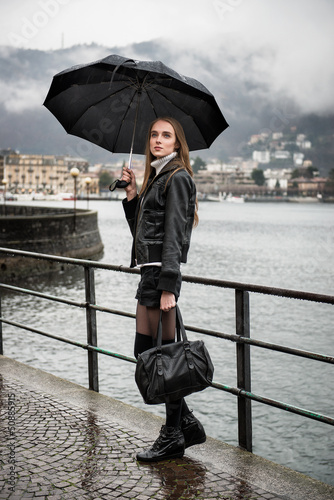 Woman walking with umbrella under the rain